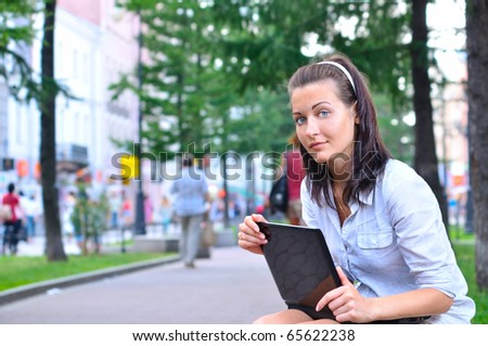 beautiful woman is sitting in city with laptop and looking at camera