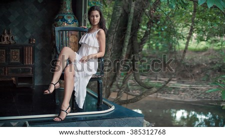 Beautiful woman is sitting on the old wooden chair on the tropical garden background. - stock photo