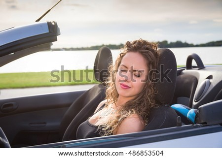 beautiful woman is sleeping in a car in summer sunny day