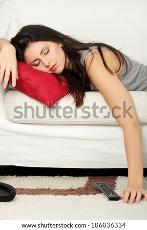 Beautiful woman is sleeping on red pillow. Pretty girl fall asleep on the couch during watching television. - stock photo
