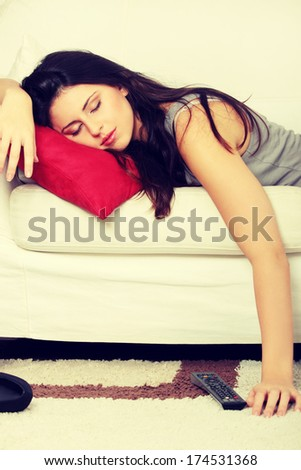 Beautiful woman is sleeping on red pillow. Pretty girl fall asleep on the couch during watching television.