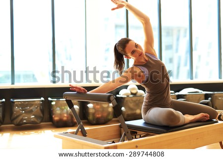 Beautiful woman is stretching her upper side of the body - stock photo