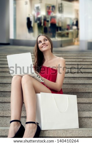Beautiful woman is surprised looking at her laptop, while sitting on the stairs with shopping bag - stock photo