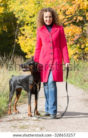 Beautiful woman is walking with a dog in autumn park.