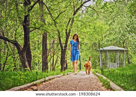 Beautiful woman is walking with dog in summer park - stock photo