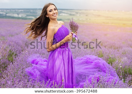 Beautiful woman is wearing fashion purple dress holding bouquet of flowers on the nature in lavender field