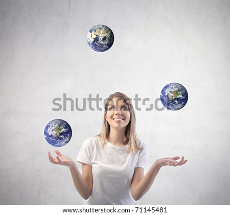 Beautiful woman juggling with earths - stock photo