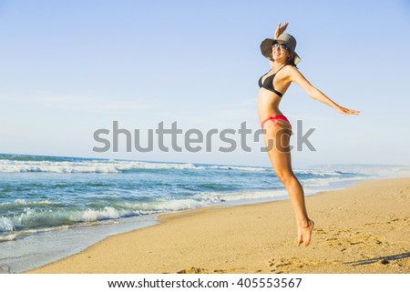 Beautiful woman jumping on the beach