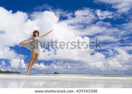 Beautiful woman jumping on the wonderful beach of Praslin, Seychelles - stock photo