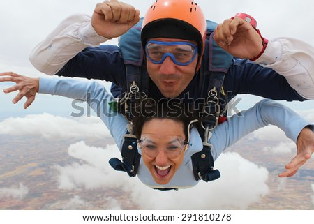 Beautiful woman jumping with a parachute , smiling in a wonderful sky. Skydiving - stock photo