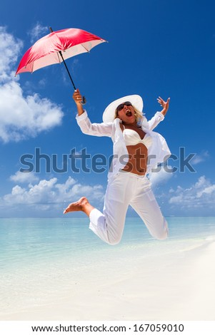 Beautiful Woman jumping with a red umbrella on the tropical beach  - stock photo