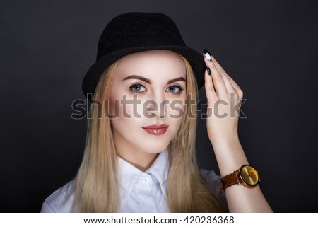 Beautiful woman lady model wears fashionable black hat, formal white blouse. Bright blond long straight hair. beauty girl face professional makeup. Portrait closeup, luxury wrist watch on her hand - stock photo