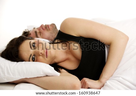Beautiful woman laid in a white bed awake next to her sleeping boyfriend isolated on a white background
