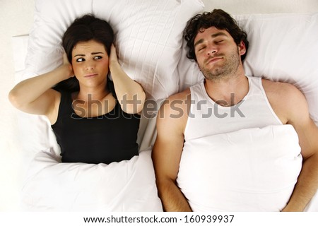 Beautiful woman laid in a white bed awake next to her sleeping snoring boyfriend isolated on a white background
