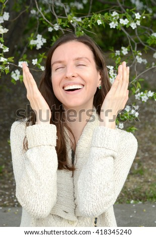 Beautiful woman laughing with closing eyes, on a background of a blossoming tree - stock photo