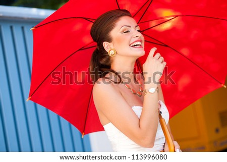 beautiful woman laughing with perfect skin wearing professional make-up holding a red umbrella - stock photo