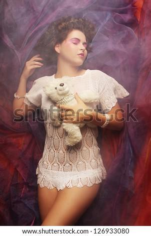 beautiful woman lay on organza with teddy bear - stock photo