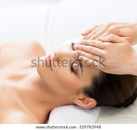 Beautiful woman laying on a mat in massage salon. - stock photo
