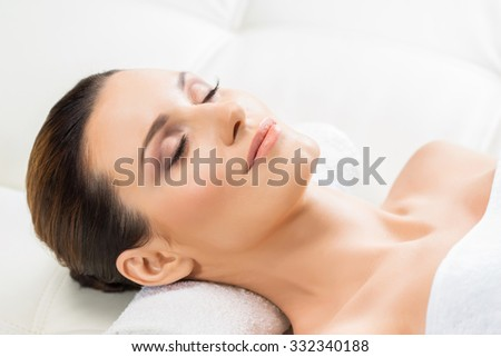 Beautiful woman laying on a mat in massage salon.