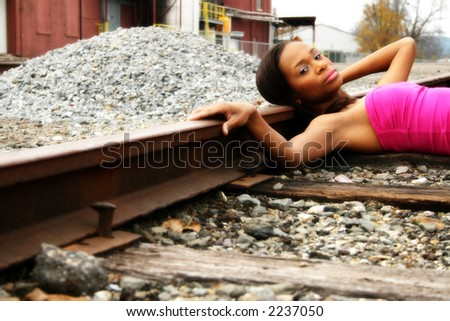 Beautiful woman laying on railroad tracks. - stock photo