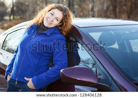 Beautiful woman leaned to car smiling and looking at camera - stock photo