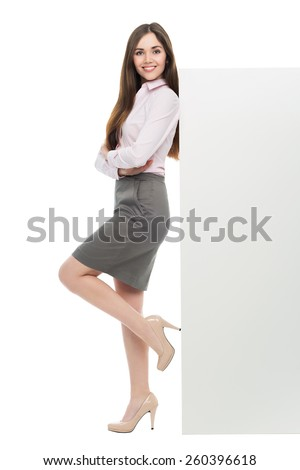 Beautiful woman leaning against big white poster  - stock photo