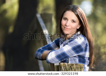Beautiful woman leaning on fence - stock photo