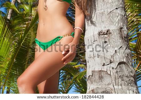 Beautiful woman legs at beach near palm tree. - stock photo