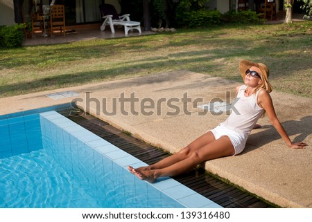 beautiful woman legs, sunbathing, woman in sunglasses enjoying the sun near swimming pool - stock photo