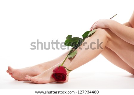Beautiful woman legs with red rose isolated on white background - stock photo