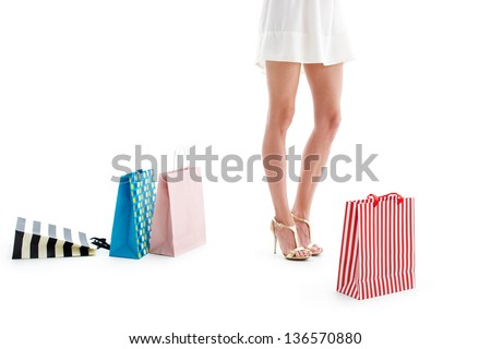 Beautiful woman legs with shopping bags isolated on white background