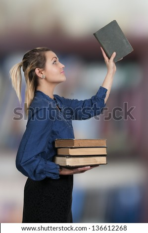 Beautiful woman librarian with some library books - stock photo