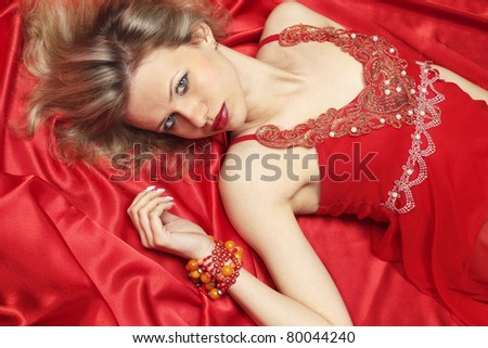 Beautiful woman lies at the red linen