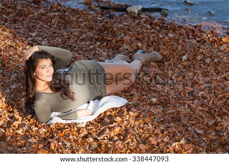 Beautiful woman lies on leaves in autumn landscape