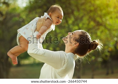 Beautiful woman lifts high her adorable baby up mid air and looks at her smiling. Happy parent spending time playing with daughter in park at sunset. Medium shot - stock photo