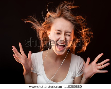 Beautiful Woman Listening Music and screams on a dark background - stock photo