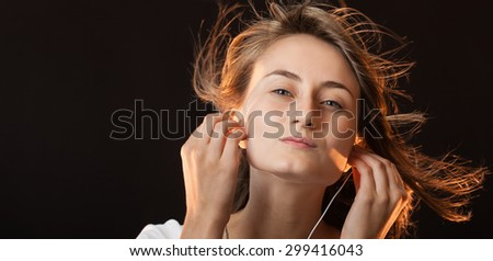 Beautiful Woman Listening Music on a dark background with copy-space
