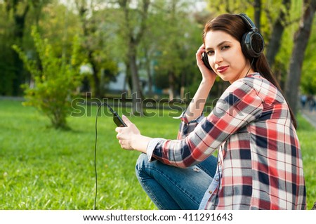 Beautiful woman listening music on smartphone sitting by the tree in park in a spring day with copy space