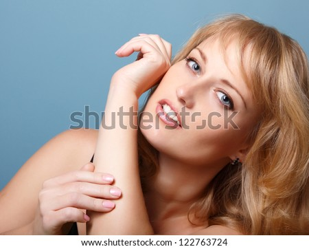 beautiful woman looking at camera, mid adult female face and hands, isolated on blue background - stock photo