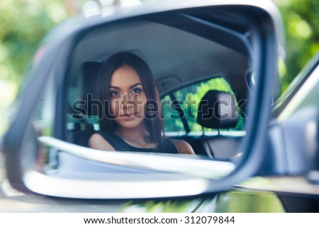 Beautiful woman looking at her reflection in a car mirror - stock photo
