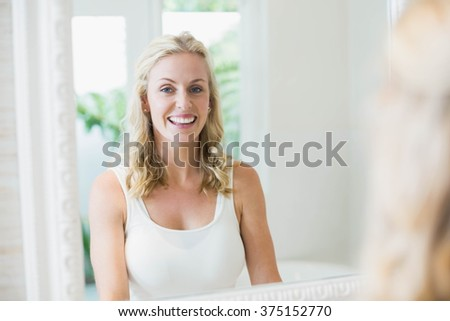 Beautiful woman looking at herself in the mirror in the bathroom - stock photo