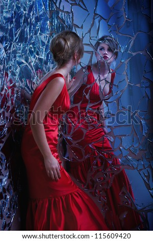 beautiful woman looking at the broken mirror