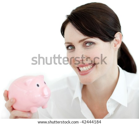 Beautiful woman looking at the camera holding a piggy bank