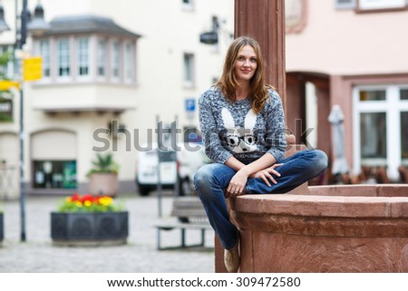 Beautiful woman looking at the camera in german city, outdoors - stock photo