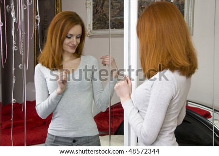 Beautiful woman looking at the mirror - stock photo