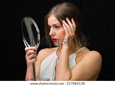Beautiful woman looking at the round cosmetic mirror - stock photo