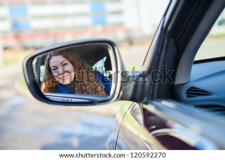 Beautiful woman looking in car back rear-view mirror sitting in vehicle - stock photo
