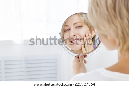 Beautiful woman looking in the mirror in the morning and smiling - stock photo