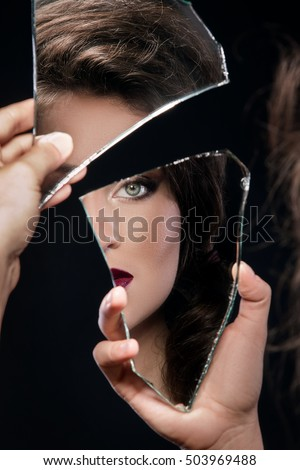 Beautiful woman looking in the piece of mirror