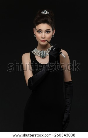 Beautiful woman looking like Audrey Hepburn standing with cigarette-holder - stock photo